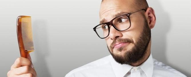 homem calvo olhando para um pente tentando entender a queda de cabelo masculina