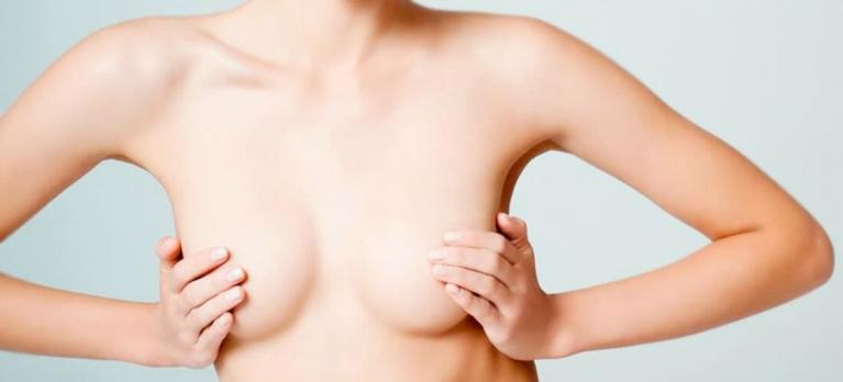 figura feminina com a mão nos seios para ilustrar a plástica de mamas